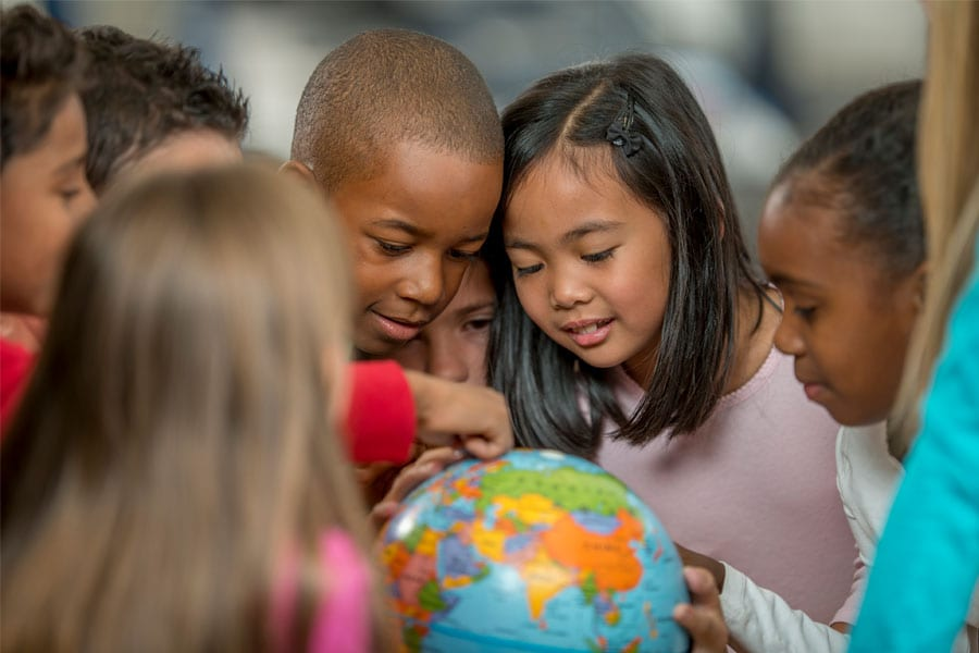 Elementary kids looking at a globe